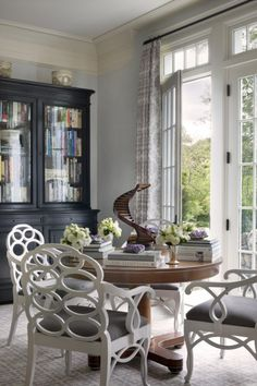 Gorgeous but informal grey dining room. Love the fretwork carpet, the round wood table, the big crown mouldings, the french doors, and of course the wondewrful white Elkins chairs with grey upholstery.