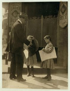 ¿Puedes describir lo que está pasando en esta imagen? Newsgirls deliver newspapers in 1910. Public domain photograph by Lewis Hine