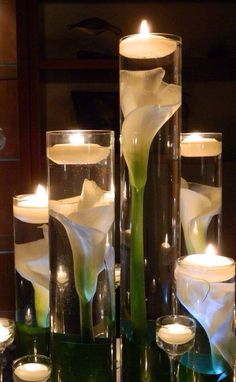 Calla Lillies submerged in cylinder vases with floating candles   I love how they appear magnified.