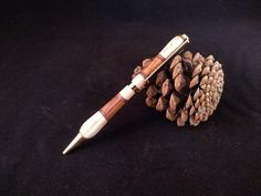 This pen is made of slices of teak, American walnut and ash wood and turned into shape on the lathe. The pen is finished with linseed oil and shellac. The metal parts are gold plated. This pen is made from diagonal segment of teak, black walnut and ash and turned to final shape on the lathe. The Egg Shop, Wooden Slices, American Walnut, Linseed Oil, Shellac, Teak, Craft Supplies, Plating, Hair Accessories