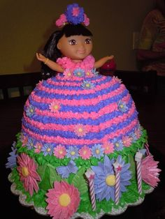 I made this dora cake for my daughters 3rd birthday. I used 2 10 inch round cakes for the base of the cake, then I used 1 10 inch cake for the bottom of her dress. Then I used a glass bowl to get the round shape for the top of her dress. Once assembled, I used a dora princess doll, and inserted the doll into the center of the cake. I then made my buttercream frosting from the wilton website. I tinted it purple, pink, and green. I used a star tip for her dress, and alternated purple and pink…