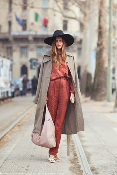 Gala Gonzalez in a black floppy hat, rust hammered silk jumpsuit, trench, and huge pink pebbled leather purse.