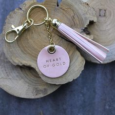"""The perfect gift to give someone sweet. A light pink, shimmery, leather keychain with a pretty tassel and reminder that their heart is golden. Tassel is approx. 3"""" long."""