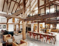 """""""We didn't want to diminish the openness and height and feeling of a great expanse of space,"""" says Arnold, though he adds, """"I was slightly concerned that we were going to end up feeling like we were reading in Grand Central Station."""" Fortunately, the barn frame's horizontal beams perform a domestic function by creating the illusion of a lower ceiling. The three major anchor beams were hewn from a single tall yellow pine.  Photo by: Raimund Koch"""