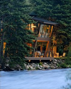 Mountain cabin with angled windows over a rushing river