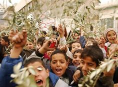 """2000 Iraqi children hold olive branches as they take part in a children's peace rally in Baghdad, Tuesday, Dec. 31 , 2002. The peace march was led by Raghda, a Syrian actress:  """"What is the new year bringing to Iraqi children? What is Santa Claus bringing them? Bombs?"""" For U.N. inspectors searching for non-existent forbidden arms, it was a normal day in which they visited seven sites, including a plant manufacturing short-range missiles and a medical research center. WMDs were never found."""