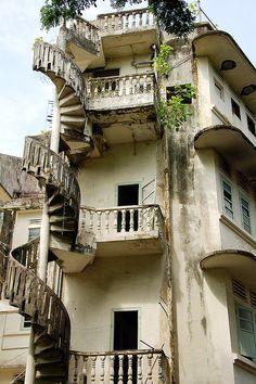 Заброшенный дом и разрушающаяся винтовая наружная лестница. С каждого витка есть переход на балкончик и к двери входа на этаж.