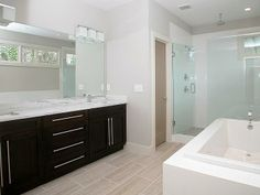 This master bathroom features custom espresso cabinetry with double square vanities and grohe fixtures, brick laid tile floor (18x24 forum silver), an oversized soaking tub and a tile shower (18x24 gloss white walls & 2x2 bellagio villa floor), double shower heads including rain shower, built-in bench and frameless glass shower wall and door.