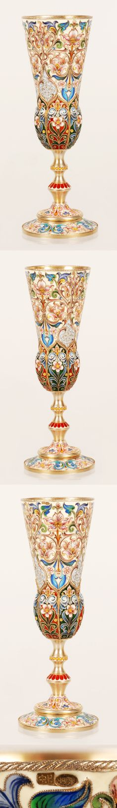 A Faberge gilded silver and shaded cloisonne enamel champagne flute, Feodor Ruckert, Moscow, circa 1900. Of tapering form, the lower section of the goblet gadrooned and decorated with applied cables, the stem with two knops, the upper body enameled with brightly colored, stylized floiage against a cream ground, set on a spreading foot similarly enameled