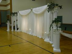 Wedding Backdrop. Defintely the swag at the top in brown tulle with the pillars on each side. No plants on the side of backdrop.