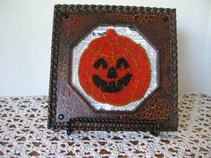 vintage frame painted with crackle-finish black and orange paint, filled with a beaded jack-o-lantern coaster on a dictionary background