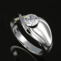 Flowing semi bezel set brilliant cut diamond solitaire. Peek a boo side view, concave mirror-maximum scintillation. A diamond solitaire so beautifully sculpted - it could be in a museum.