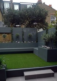 Raised beds grey colour scheme agapanthus olives artificial grass porcelain grey tiles yellow stock brick walls grey Floating bench Balham Clapham Wandsworth
