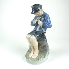 A Royal Copenhagen Whittler porcelain figure by Christian Thomsen, circa 1969 - 1974. A Royal Copenhagen Whittler porcelain figure by Christian Thomsen, circa 1969 - 1974. Modelled depicting a seated boy whittling a stick, marked beneath with the green Royal Copenhagen Denmark stamp, three wavy lines in blue and numbered 905. 7.3 in (18.5 cm) height.