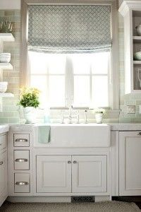 kitchen window, sink and open shelving on one side and cabinet on other.