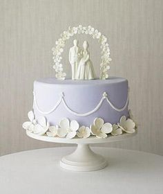 Single-tier cakes are all the rage. Give your cake drama with an arch of petit flowers and a bride and groom topper made of white chocolate.