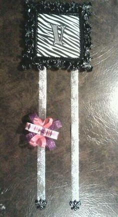 Zebra bow holder. Frame hangs on wall or door.  Backing is stuffed (jewel tipped blunt pins can hold pictures, hair bands, or notes for more customization). Hanging ribbons weighed down by resin fleur-de-lis. Sequin initial. Adds a functional and personalized touch to little girls' room. Colleen Chriss custom creation.