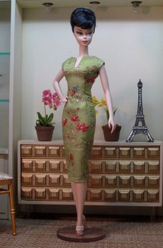 A slim fitting silhouette in a stylish Chinosoiserie print of bamboo and flowers on a wasabi green ground. The neckline is split and flowers and leaves are picked out in tiny seed beads. The dress is fully reversible to the vibrant coral silk interior. A belt in the print picks up the band of print at the hem. An elegant and versatile sheath. This sheath fits Silkstone Barbie, Poppy Parker, and Nu Face dolls.