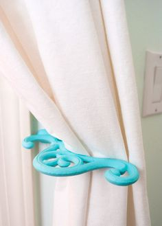 repaint a plant hanger, turn it on its side, and use it for a curtain hook...love!