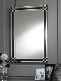 This Art Deco mirror features a fascinating design - each edge of the border is made up of three strips of bevelled glass, the central one being black rather than clear; and each corner is a 3x3 clear and black checker board design, again using bevelled glass. http://www.chicconcept.co.uk/1619-modern-black-check-border-art-deco-mirror.html
