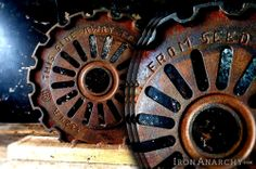 """Old gear of thick cast iron in an ornate industrial design. Engraved text to make it even more intriguing! Rustic reclaimed lumber display stand.7 5/8"""" diameter.Purchase 2 or more of these 8"""" sculptures, and your order ships domestically for free. Free international shipping on the 2nd 8"""" gear sculpture purchased when shipped together."""