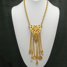 Fabulous 1960s Medieval Renaissance Revival Chatelaine Necklace with a large gold tone plated medallion decorated with Grecian designs on both front and back. 9 long gold tone chains with Grecian style charms gracefully swing from the beautiful medallion.