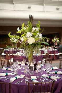 Love these wild green floral centerpieces with the purple table clothes!