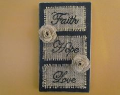"""Distressed, Black, Wooden Wall-hanging That Says """"Faith, Hope, Love"""" Written on Burlap in a Cursive Font with Two Burlap Flowers"""