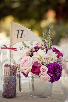 Table #'s are bottles of dried Rose buds with a burlap flag. . Cute!
