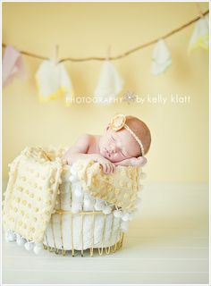 Newborn with washclothes on a clothesline and basket used as props. I love this idea and the soft colors. {Baby Photography} {Newborn Poses} {Prop Ideas} {Newborn Photo Session Ideas} {Birth Announcement Idea}