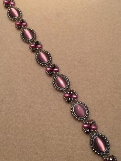 Pink Cats Eye w/metal base, Silver Seed Beads, Pink Superduos, Silver Lobster Claw Closure. Measures approximately 8 inches long and inch wide. Diy Beaded Rings, Beaded Braclets, Seed Bead Bracelets, Crystal Bracelets, Seed Beads, Beaded Necklace Patterns, Diy Jewelry Projects, Homemade Jewelry, Bracelet Tutorial