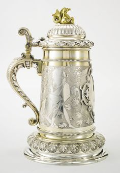 """A monumental Russian parcel gilt tankard, Konstantin Linke, Bolin, Moscow, 1893 tapering cylindrical, the body with engraved and polished views of Klodt's """"The Horse Tamers"""" from St. Petersburg's Anichkov Bridge set with scrolling laurel and oak on a stippled ground, the hinged domed lid with a band of berried laurel and surmounted by gilt hippocampus finial, the scrolling handle with conforming ornament, the front applied with an oval cartouche engraved with Cyrillic initials, the stepped…"""
