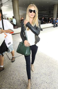 Rosie Huntington-Whiteley in Dolce and Gabbana sunglasses, Saint Laurent bag and boots.  (July 2014)
