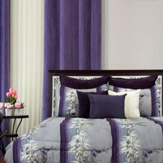A three piece grey and purple comforter set. The shams bring out the vibrant purple stripes to help set the tone.