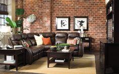 parement mural en brique rouge, canapé d'angle en cuir marron foncé et table basse assortie