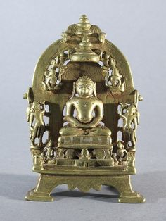 A Jain Brass Shrine, Gujarat, western India, circa 15th century <br> With central figure of a seated tirthankara on a raised cushion flanked by chauri bearers, a canopy and apsarases above, surmounted by twin kalasa finials, enhanced with silver and copper inlay, a fragmentary dedicatory inscription in devanagari on the reverse <br> 14cm high <br> ++Worn and slightly pitted in places, one or two knocks <br>
