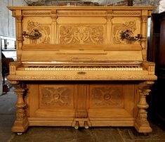 An art cased, Hupfer upright piano with an ornately carved Classical style, oak case at Besbrode Pianos. The Classical style is seen in the symmetry and proportion of the design with strong Greek and Roman influences. Piano features ornately carved pilasters, shells, scrolling acanthus and flowers.