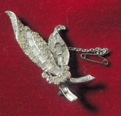 B10778 £SOLD (Oct 2016) A vintage Art Deco diamante brooch (baguettes and round) in the form of a flower or leaves, together with safety chain. The brooch measures just over 2.375in top to bottom and just under 1in wide in total at its widest. Weighs just under 11g. Exact age unknown but probably dates from the first part of last century, possibly 1920s or 1930s.