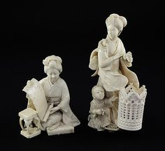 Two Japanese ivory okimono of bijin, Meiji period, the first of a kneeling lady holding a scroll by a table and box, engraved two character signature, 9.5cm., the second a standing bijin with a kneeling boy by her feet, later mounted with an ivory dice shaker, 15cm.