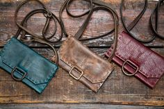 CIBADO leather bags - Entirely hand sewn brown, red & teal leather wallets on cross body length strap incorporating vintage/old/used horse tack to become handle and vintage hardware for decorative detail. Horse tack sourced from barns all over Colorado.