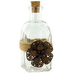 "Add simple and beautiful decorative pieces to your home or office. Twine Wrapped Small Bottle with Antique Flower features a cork stopper, a ribbon of twine, and a large antique brown metal flower. This glass bottle is perfect for adding to bookshelves, mantels, desks, and more.    	     	Dimensions:    	  		Length: 1 3/4""  	  		Width: 1 3/4""  	  		Height: 4 3/4""      	     	For decorative use only."