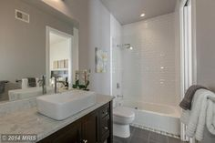 Contemporary Full Bathroom with SomerTile Victorian Soho Subway White Porcelain Tiles (Case of 100 $79.99), bathtub glass screen ($299), limestone tile floors, marble counter, vessel sink, earl grey paint Sherwin Williams.
