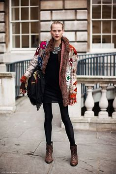 Model off duty in a fur lined textured embroidered coat.