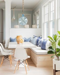 Coastal styled kitchen nook with light wood built-in bench and white Eames chairs + blue accents   K Marshall Design