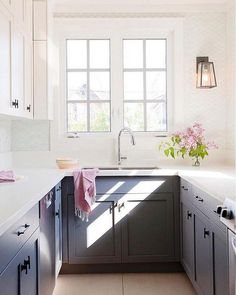 Small, narrow white and gray kitchen boasts white upper and gray lower shaker cabinets topped with white quartz countertops.