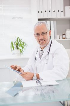 Buy Smiling doctor using a tablet pc in medical office by Wavebreakmedia on PhotoDune. Smiling doctor using a tablet pc in medical office