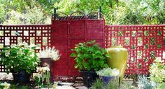 To hide an ugly chain link fence, this gardener bought a standard wood lattice, artfully cut out portions to create a pattern, then stained the whole thing. A tri-fold rattan screen was stained the same color, reflecting light back into the garden and further camouflaging the chain link. Photo: Susan Morrison and Rebecca Sweet