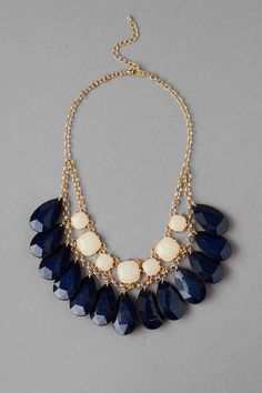 """This+fascinating+statement+necklace+features+faceted+navy+teardrops+that+hang+beneath+a+row+of+ivory+stones+to+create+an+elegant+look.+Finished+with+a+lobster+claw+clasp.<br><br>  -18""""+length<br>  -3""""+extension<br>  -Lead+&+nickel+free<br>  -Imported<br>+"""
