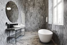 Extravagant modern bathroom with marble walls and bathtub at Nobis Hotel Copenhagen