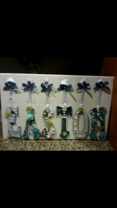 Baby shower gift. Each letter comes off the cardboard so the parents can hang them how they want. Homemade even the thumbtacks are decorated
